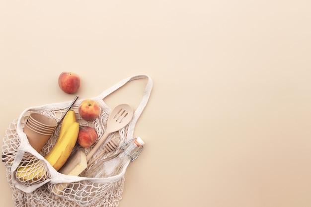 エコショッピングバッグフルーツとベージュの背景に環境にやさしい夏のコンセプト