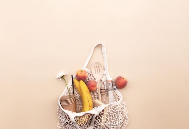 環境にやさしい夏の概念的なフラットは、エコショッピングバッグ、キッチンリサイクルカトラリー、水のガラス瓶、バナナとリンゴ、紙のカップ、スポンジでベージュの背景に横たわっていました。高品質の写真