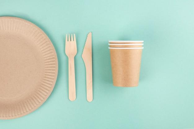 青い背景の環境に優しい食器、紙皿とグラス、木製のフォークと名前、上面図
