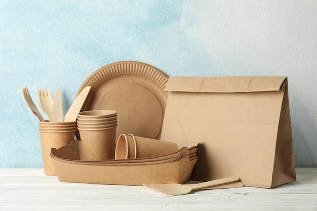 Eco - friendly tableware and paper bag on wooden table, space for text