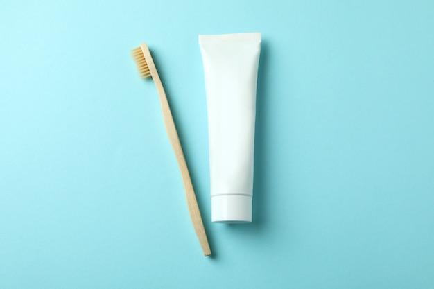 Экологичная зубная щетка и тюбик зубной пасты на синем