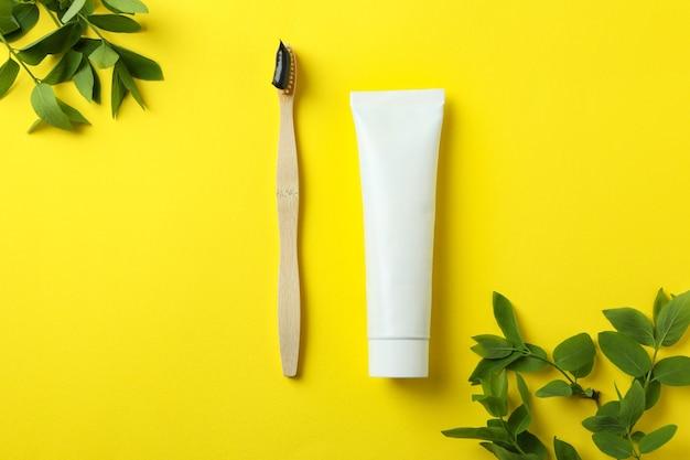 黄色の背景に環境に優しい歯ブラシ、歯磨き粉、枝