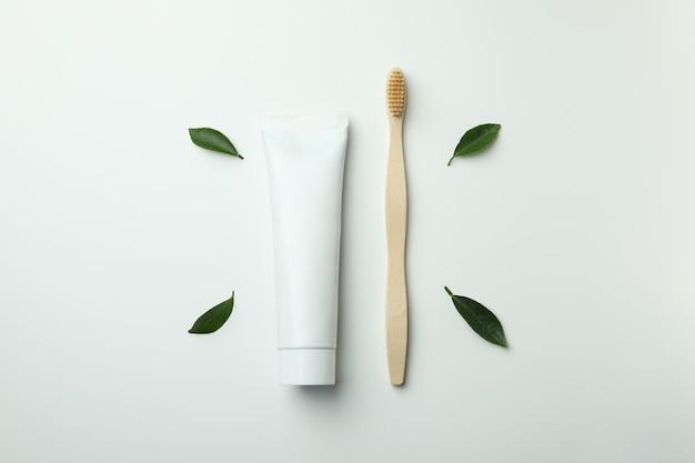環境にやさしい歯ブラシ、歯磨き粉のチューブと白い背景の葉