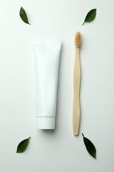Экологически чистая зубная щетка, тюбик зубной пасты и листья на белом фоне
