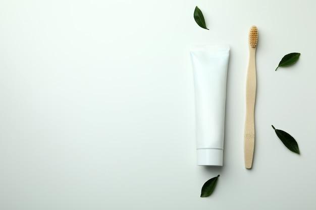 Экологичная зубная щетка, тюбик зубной пасты и листья на белом
