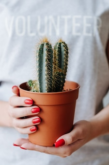 Eco friendly volunteering. nature care and protection. woman with volunteer sign hold cactus.