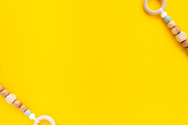 Eco-friendly wooden children's toys on a bright yellow background, top view, flat layout, copy space for text.