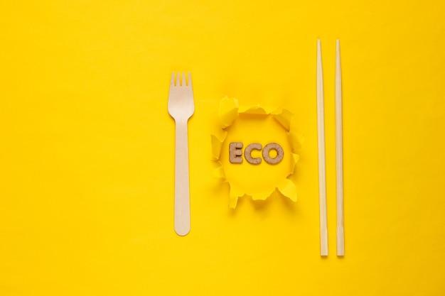黄色の背景に環境に優しい木製フォークと箸。破れた穴の紙にエコという言葉。ミニマリズム。