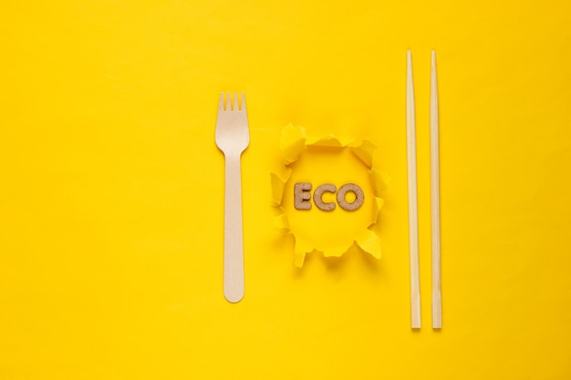 Eco-friendly wooden fork and  chopsticks on yellow background. word eco on torn hole paper. minimalism.