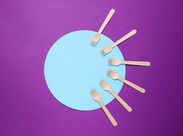青い円と紫色の背景に環境に優しい木製フォーク。