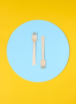 青い円と黄色の背景に環境に優しい木製フォーク。