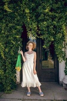 環境にやさしい。彼女の手で緑のメッシュバッグを保持している白いロングドレスの若い女性
