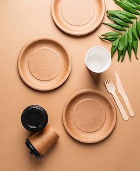 Экологичная одноразовая посуда с нулевыми отходами, вид сверху, плоская лежала на коричневом фоне