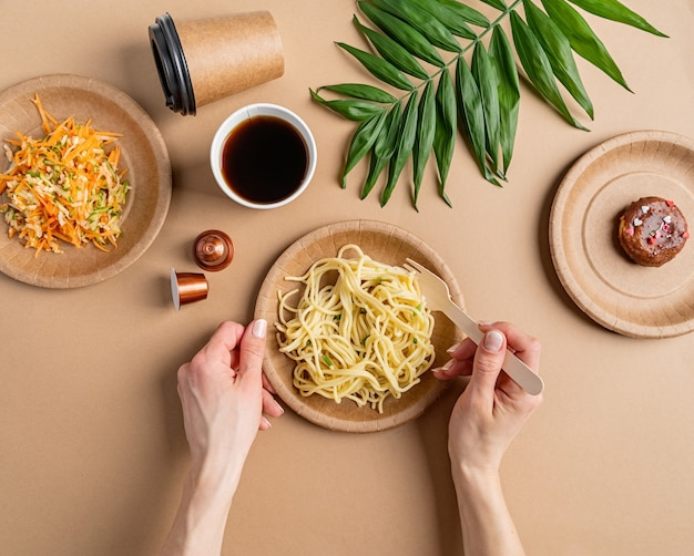 Eco friendly zero waste disposable tableware with pasta, salad and donut top view flat lay on brown background