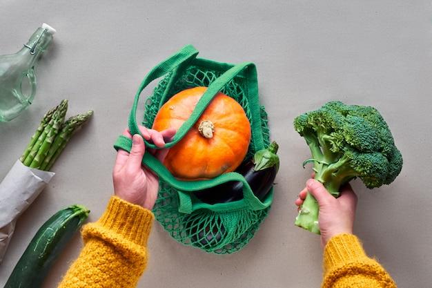 環境にやさしいゼロ廃棄物の平置きは、オレンジ色のカボチャが付いたストリングバッグを手で保持します。緑とオレンジ色の野菜と手でペーパークラフトにフラットを置きます。