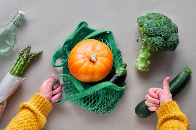 環境にやさしいゼロ廃棄物フラットレイは、オレンジのカボチャが付いたストリングバッグを手で持っています。フラットは緑とオレンジ色で、野菜とペーパークラフトに手を置いた。