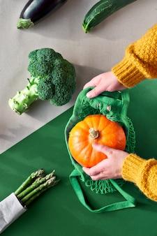 エコフレンドリーなゼロ廃棄物フラットブロッコリーとオレンジ色のカボチャのストリングバッグを両手で置きます。 2つの色の紙の壁、クラフトペーパー、グリーンに野菜を添えて、平らに寝かせます。