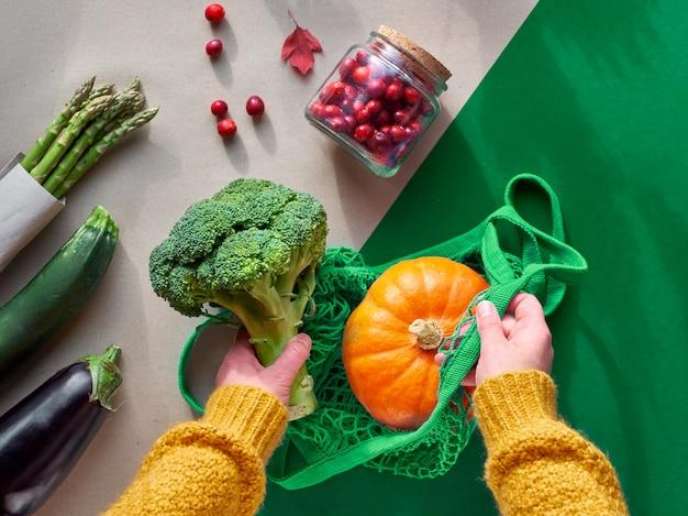 エコフレンドリーな廃棄物ゼロフラットブロッコリーとオレンジ色のカボチャと文字列の袋を保持している手で横たわっていた。 2つの色、クラフト、グリーンペーパーにガラスの瓶に野菜とクランベリーのフラットレイアウト