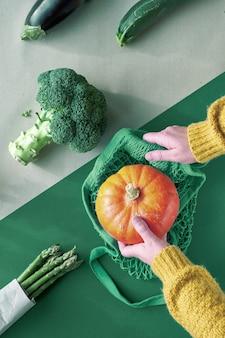 エコフレンドリーなゼロ廃棄物フラットブロッコリーとオレンジ色のカボチャのストリングバッグを両手で置いてください。