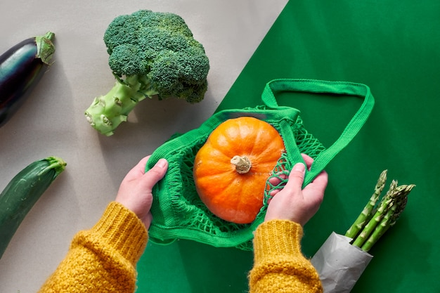 Eco friendly zero waste flat lay with hands holding broccoli and string bag with orange pumpkin.autumn or spring top view with vegetables on two color paper , craft paper and green.