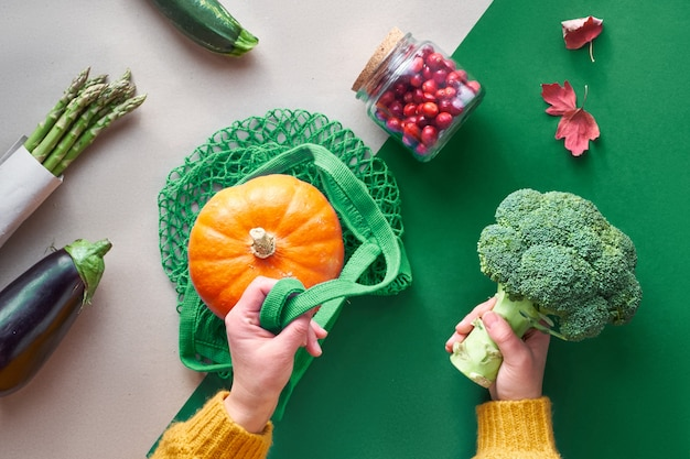 Eco friendly zero waste flat lay with hands holding broccoli and string bag with orange pumpkin. fall flat lay with vegetables and hands on craft paper background, text space.