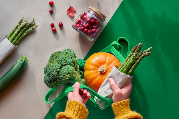 Eco friendly zero waste flat lay with hands holding broccoli and string bag with orange pumpkin. flat layout with vegetables and cranberry in glass jar,