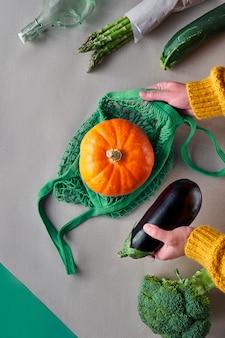 そこにナスを置くためにオレンジ色のカボチャで文字列バッグを持っている手で環境に優しいゼロ廃棄物フラットレイ。フラットは、野菜とクラフトペーパーに手を置いた。