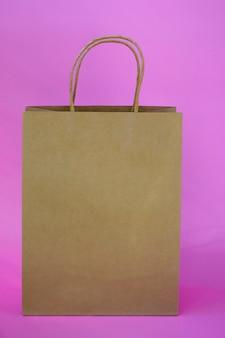 色付きの背景にコピースペースのあるエコギフトバッグ。縦の写真