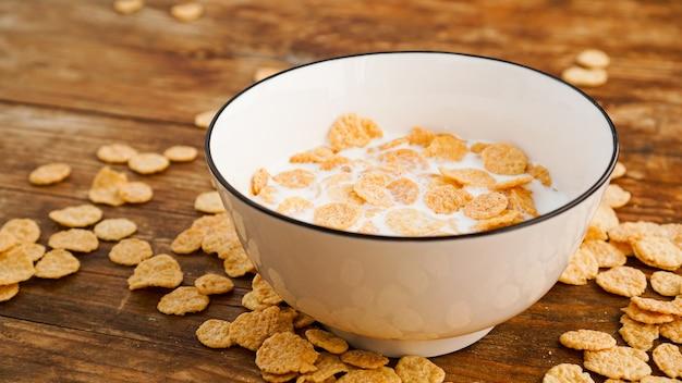 エコ健康食品表面。コーンフレークとミルク。白いボウルにミルクのフレーク。健康的な食事と新鮮な朝食