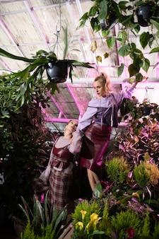 エコライフ。緑の家で写真撮影をしながら、緑の植物の中にいる美しい魅力的な女性