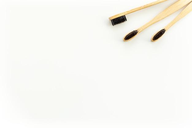 Концепция экологических материалов с бамбуковой зубной щеткой на белом