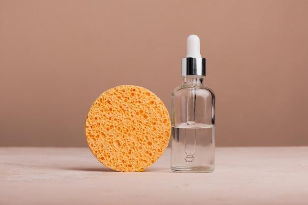 茶色の背景にピペットとオレンジ色のスポンジを備えたガラス瓶に入ったエコ ミネラル オイル