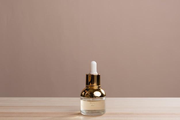 茶色の背景にピペットでガラス瓶に入ったエコ ミネラル オイル