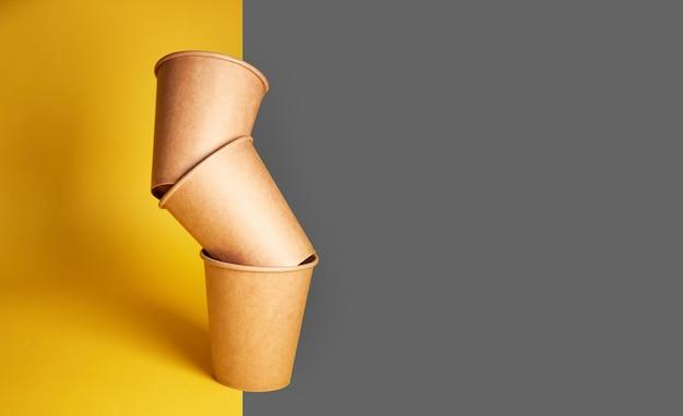 Эко натуральные бумажные стаканчики на желто-сером фоне. концепция устойчивого образа жизни