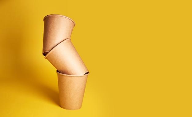 Эко натуральные бумажные стаканчики на желтой поверхности