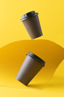 Eco paper cup, coffee paper cup on yellow background. mockup for your advertisement.