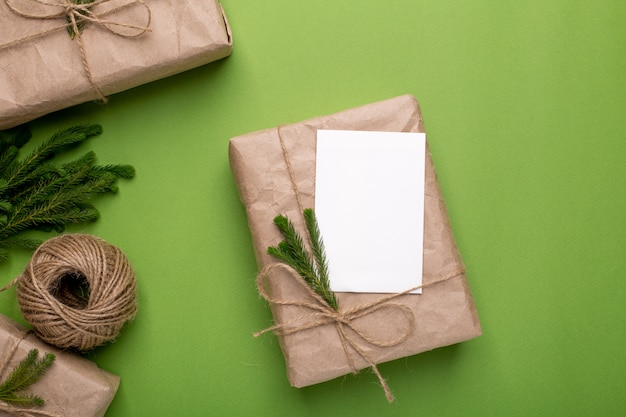 Eco present and card with green plants in craft paper on a green surface
