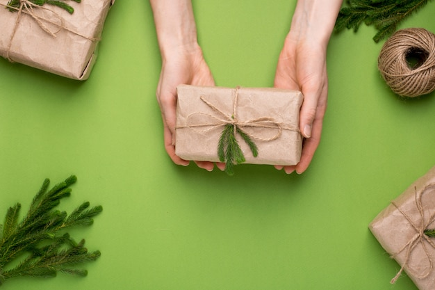 Eco present with green plants in craft paper in hands on a green surface