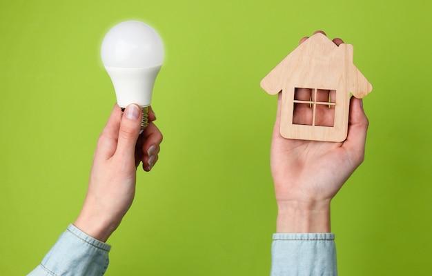 에코, 에너지 개념을 저장하십시오. 여성의 손을 잡고 녹색에 집 그림 및 전구.