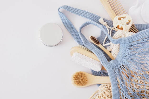 Eco set for body care in knitted bag on gray background, natural cosmetics and zero waste lifestyle, wood skin care products