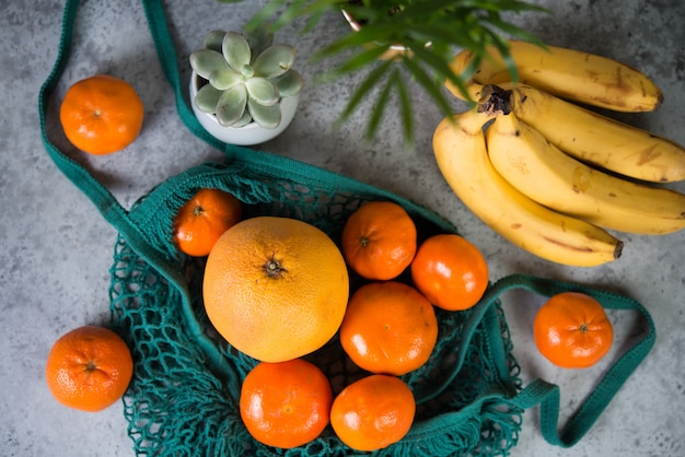 Eco shopping bag with fruit from the store on a gray table surrounded by home flowers , top view, selective focus