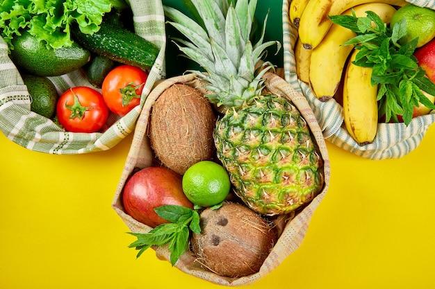Эко хозяйственные сумки с органическими фруктами и овощами на желтом фоне