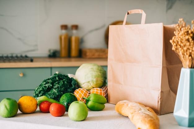 モダンなキッチンのテーブルに新鮮な野菜とバゲットが入ったエコショッピング紙袋。
