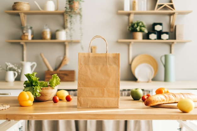Eco shopping paper bag with fresh vegetables and baguette on the table in kitchen