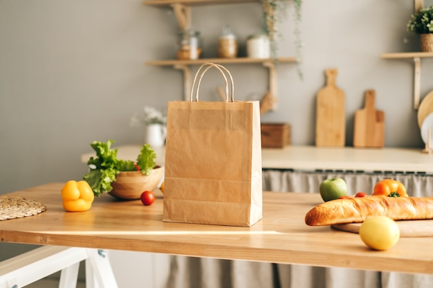 Eco shopping paper bag with fresh vegetables and baguette on the table in modern kitchen