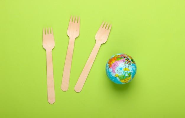 エコ静物。プラスチックフリーのコンセプト。緑の背景に木製のフォークとグローブ。上面図