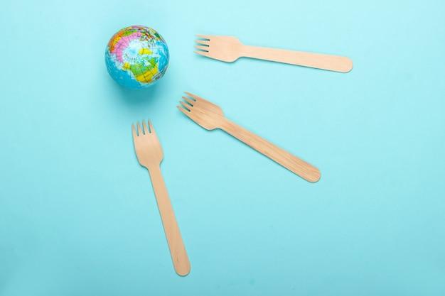 エコ静物。プラスチックフリーのコンセプト。青い背景に木製のフォークとグローブ。上面図