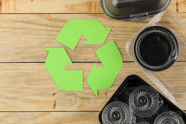 Эко-символ. утилизация отходов. экологическая концепция на натуральном деревянном столе. переработка отходов. вид сверху.