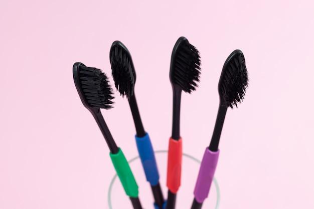 ライトピンクの背景に生分解性プラスチックと竹活性炭で作られたエコ歯ブラシ