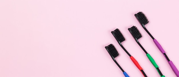 ピンクの背景に生分解性プラスチックと竹活性炭で作られたエコ歯ブラシ。コピースペース付きバナー